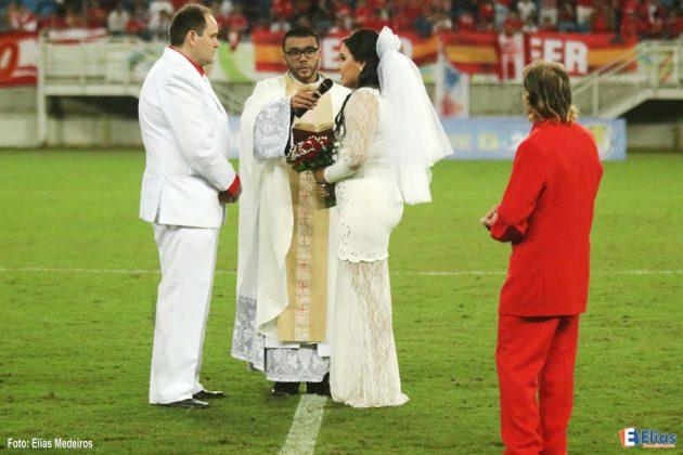 Apaixonado pelo América-RN, corretor de seguros convenceu a noiva a topar essa loucura no intervalo da partida contra o Ceilândia, na Arena das Dunas. Cerimônia durou apenas cinco minutos.